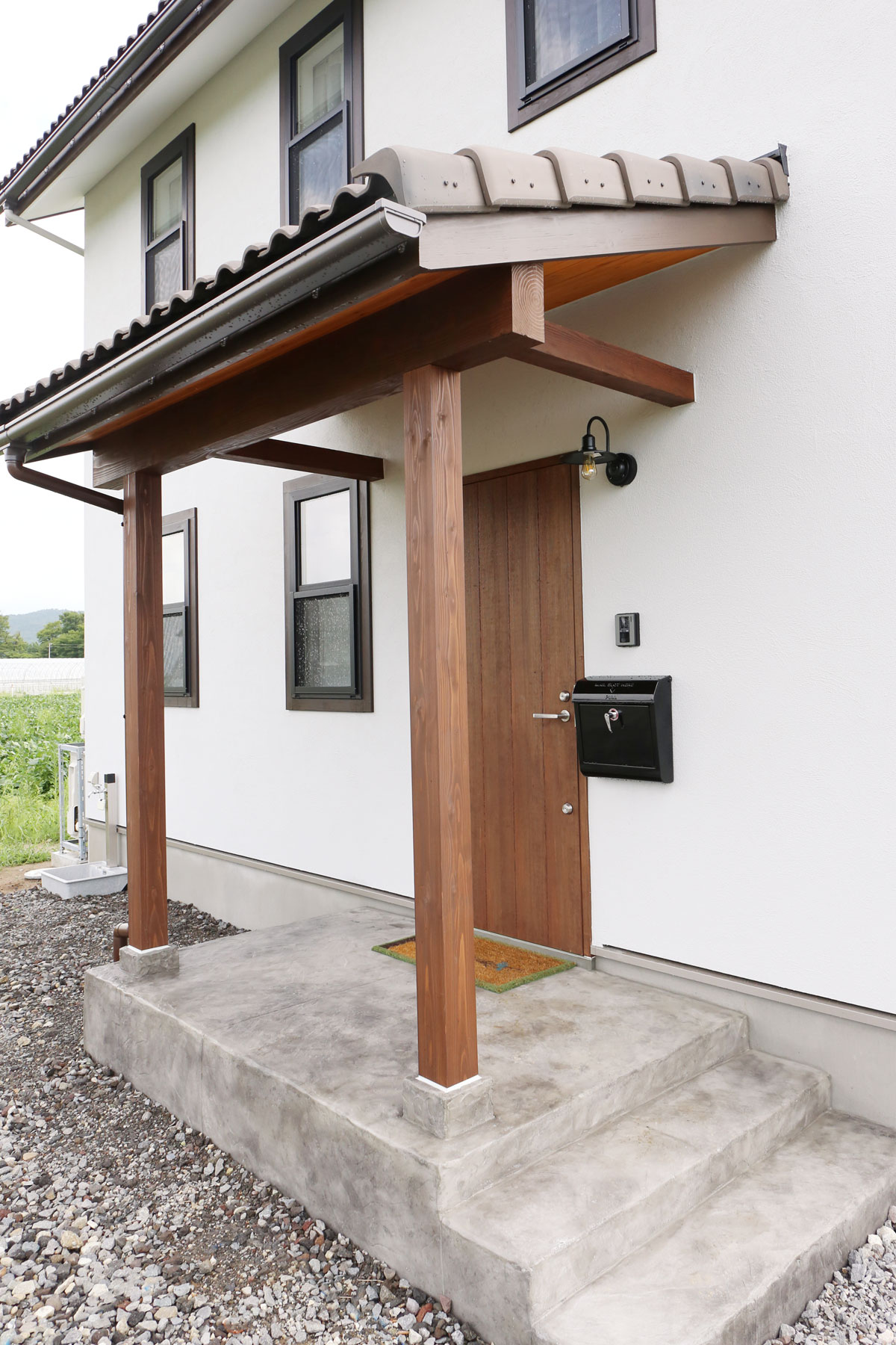 田園に佇むブルーグレーの塗壁のMamanの家。30Sタイプ。玄関ポーチ【酒田鶴岡で新築、デザイン住宅、リノベーションの工務店 ナチュラル工房伊藤住宅】