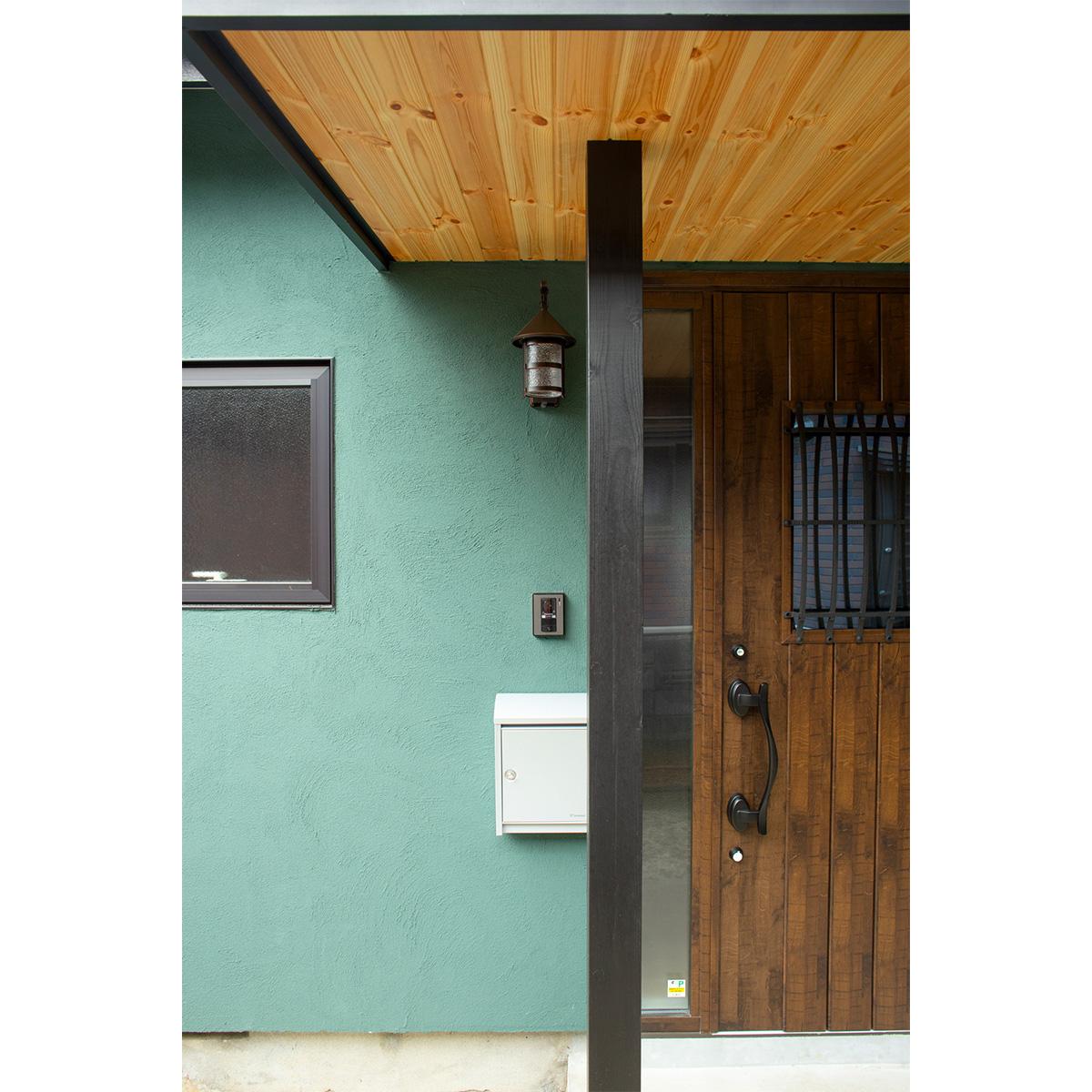 グリーンの美しい塗り壁の外壁が特徴的な玄関