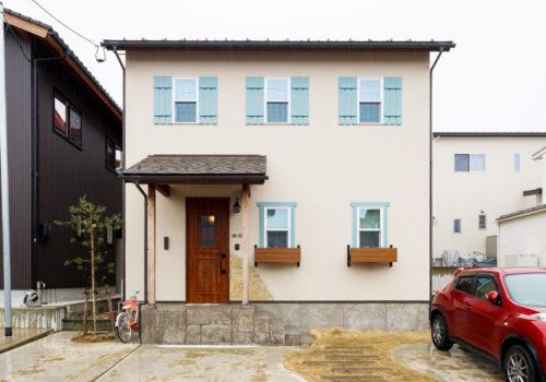 ブルーの鎧戸と窓枠がアクセントになったかわいいお家