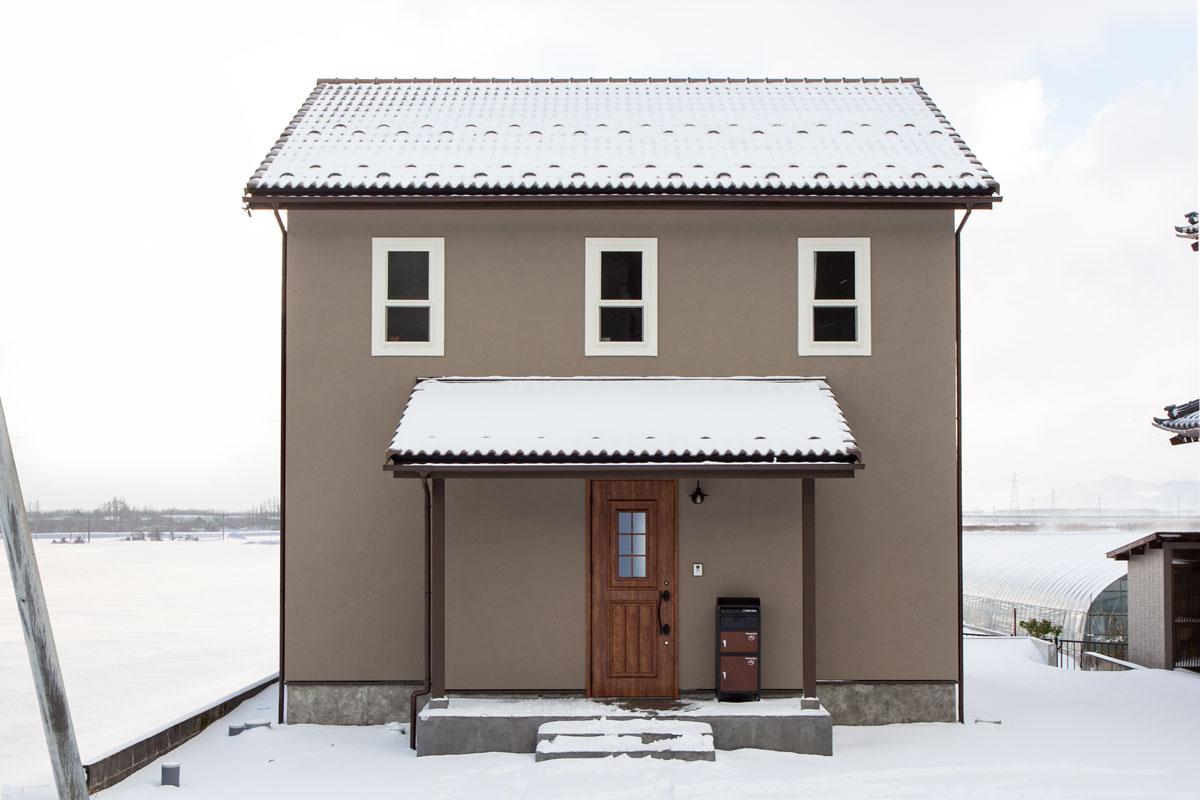 雪に映えるブラウンの塗り壁がかわいいママンの家