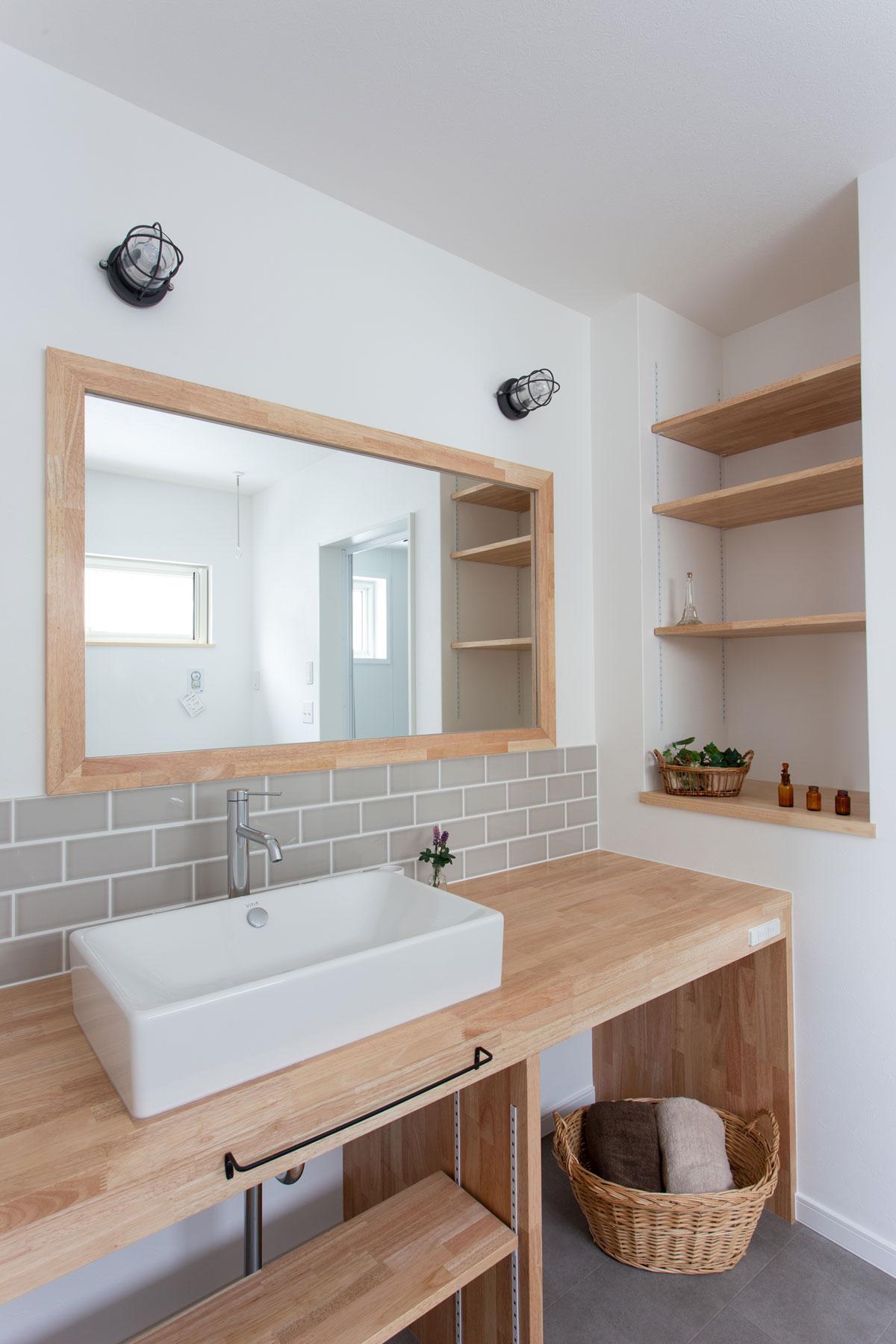 グレーのタイルをアクセントにした広々洗面スペース