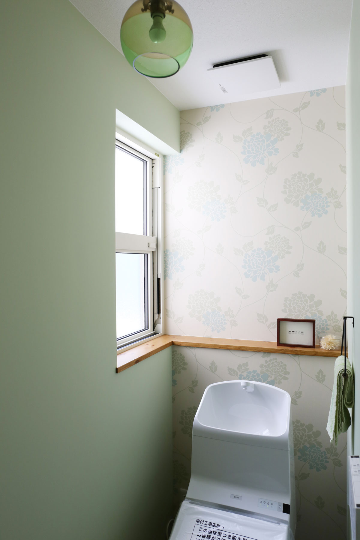 グリーンの壁紙をアクセントにしたかわいいトイレ