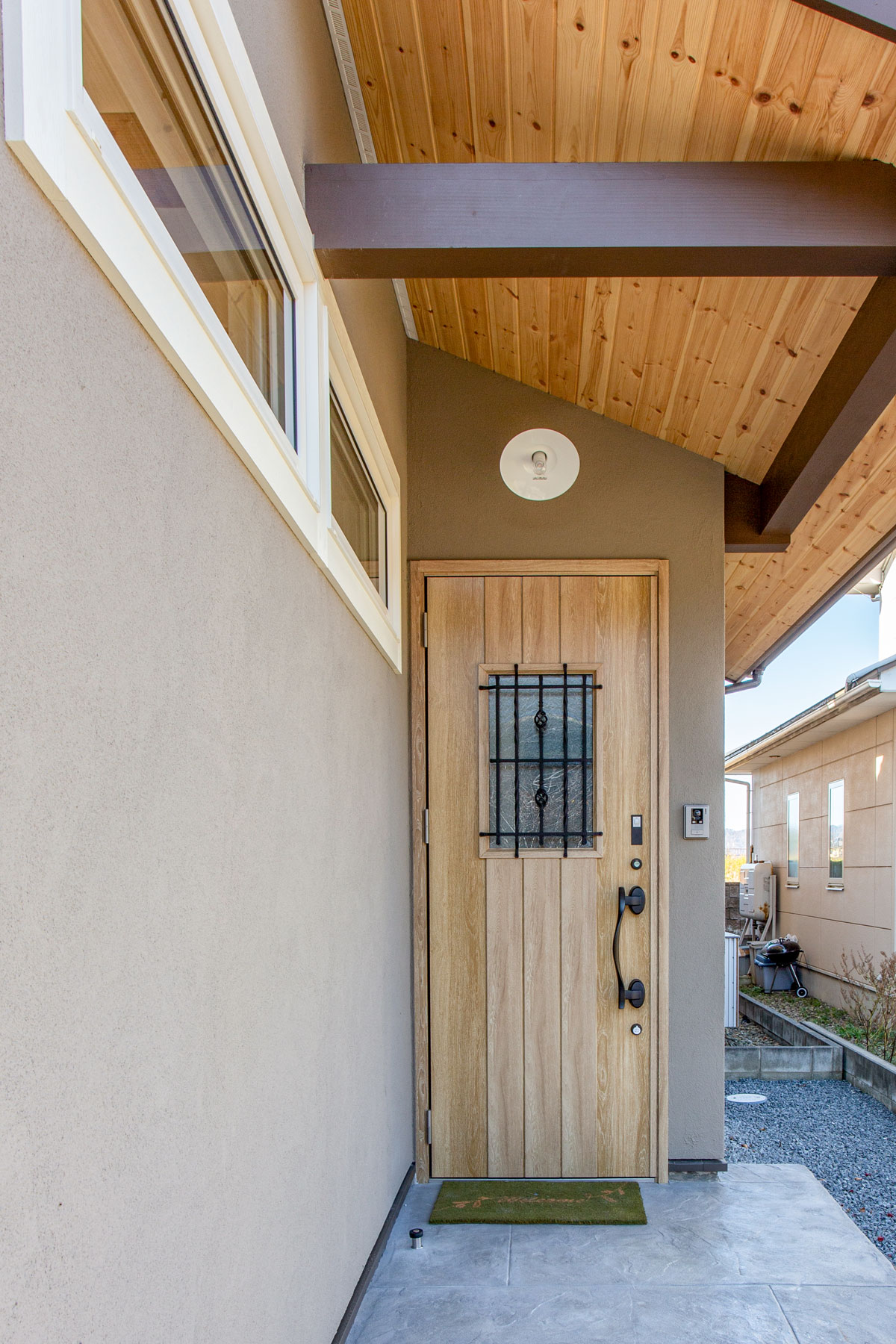 カフェオレカラーの塗り壁に合わせた玄関ドア