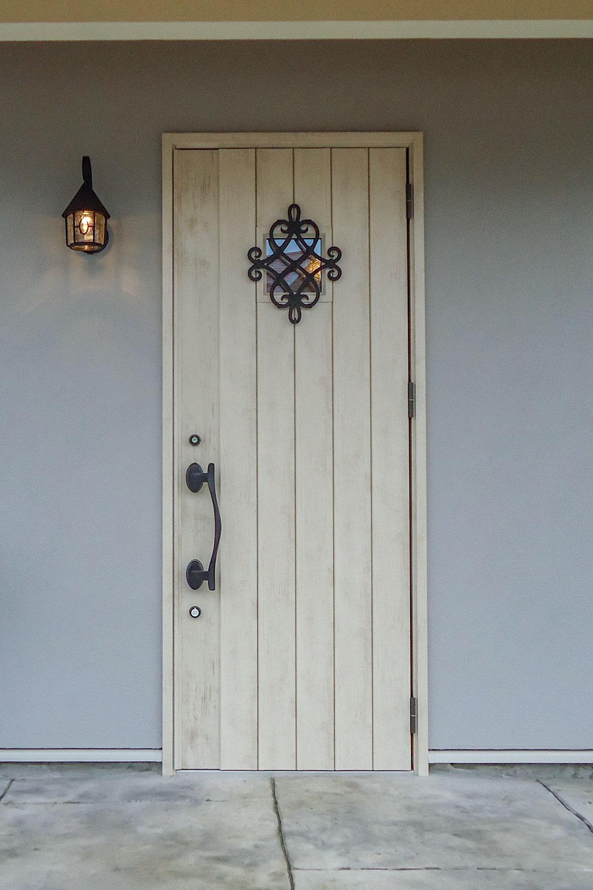 ライトブルーの塗り壁に合わせた白の玄関ドア
